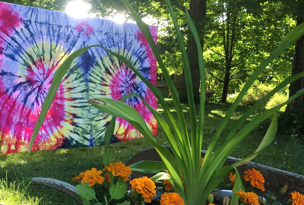 Marigolds and tie-dye tapestries hanging on the line