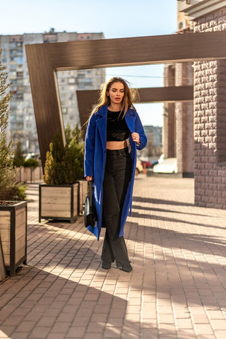 Model standing under an archway wearing the Blue Stella trench coat