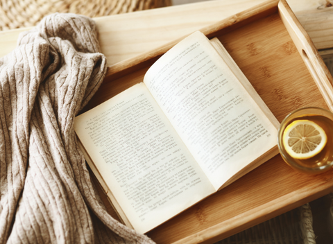 Image of a book with a glass of hot water with lemon on a wood tray with a cream blanket.