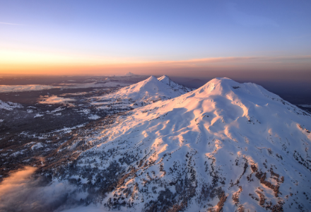 Picture of a massive snow capped mountain at sunset.