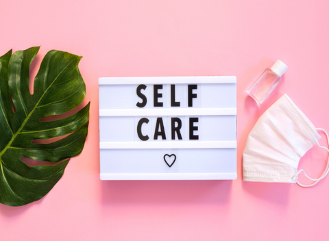 """Neon board that says """"self care"""" with a heart. Next to a large leaf and a medical face mask on a pink background"""