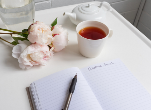 Gratitude journal with tea and pink peonies
