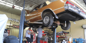 Gold car on lift with two men working on transmission swap GForce Performance parts