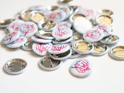 Pile of buttons with drawing of pink hand that is drawing on a white and blue background created by Loren Marple
