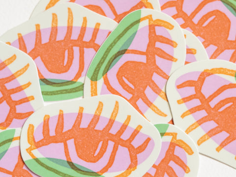 A pile of die cut stickers with drawings of orange eyes on pink, green and off-white backgrounds created by Loren Marple