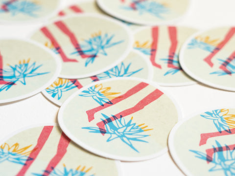 Pile of round stickers with drawings of pink feet walking by blue and orange aloe plants on an off-white background created by Loren Marple