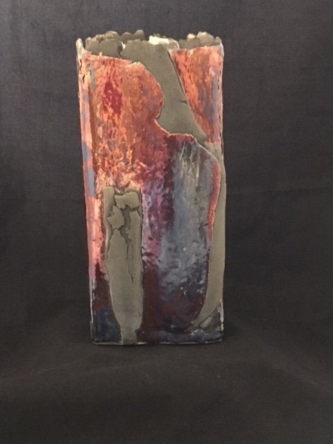 While it looks like there are two different colors or glazes on this piece, that is not the case. What you are seeing is the pattern of the flames that surrounded this vase and caused different reactions on the surface.