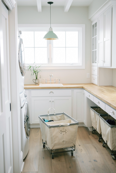 Clean and white industrial farmhouse laundry room with unique carts | Friday Favorites at www.andersonandgrant.com