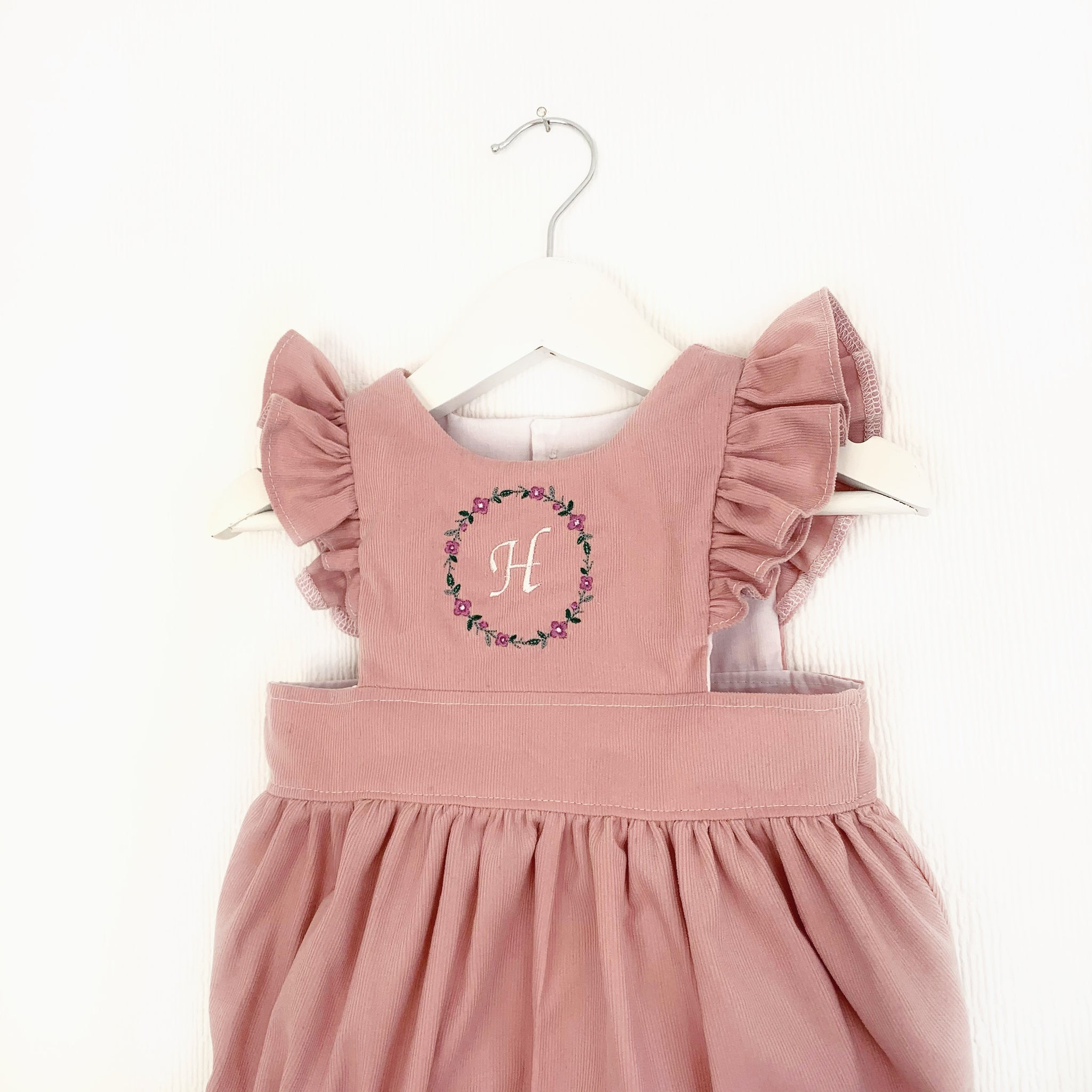 Pink needlecord pinafore; embroidered
