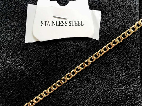 """A necklace laid over a black leather fabric with a tag that says """"stainless steel."""""""