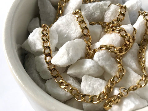 A white bowl filled with white rocks with a gold necklace laid over the top.