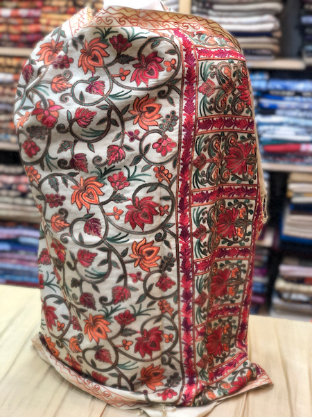 A decent beige kashmiri shawl with multi colour floral embroidery all over.