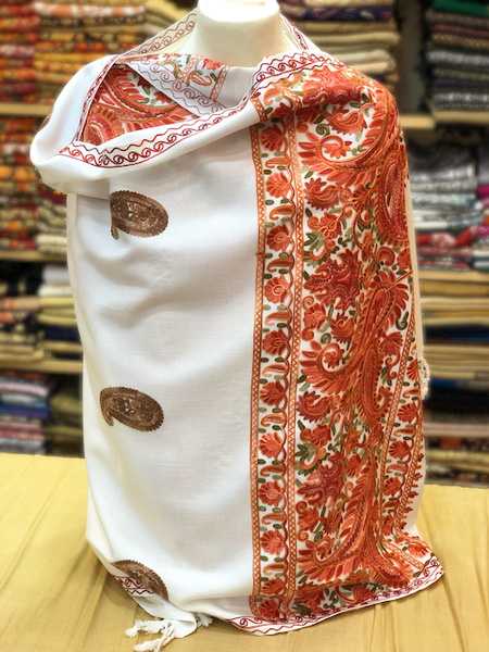 An elegant white shawl with multi colour floral embroidery on border and two tone paisly enbroidery on the body