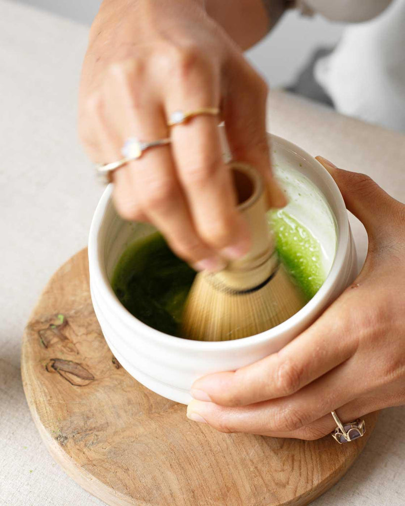 Preparing ceremonial matcha tea with bamboo whisk and white ceramic tea bowl, available at Matcha Cafe Bali