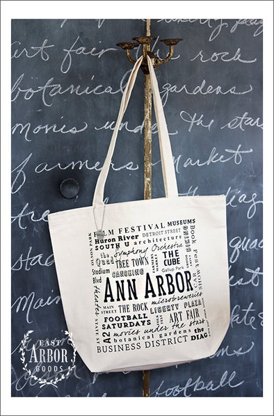 Large natural colored canvas tote bag featuring Ann Arbor, Michigan. Words in different fonts and sizes showcase local places and activities.