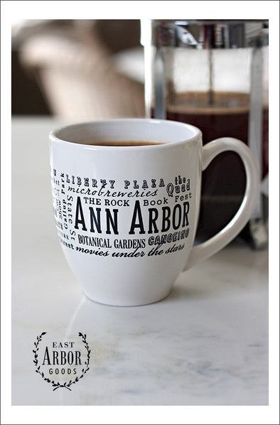 White ceramic coffee mug featuring Ann Arbor, Michigan with places and activities featured in different fonts in black screen print.