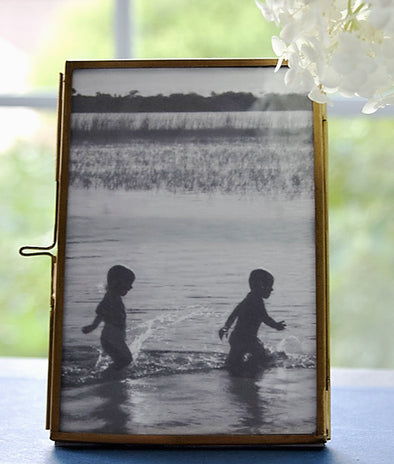 "Brass Picture Frame with a simple to open and close clasp detail. It holds a 4"" x 6"" photo and has a photo of two kids playing in water."