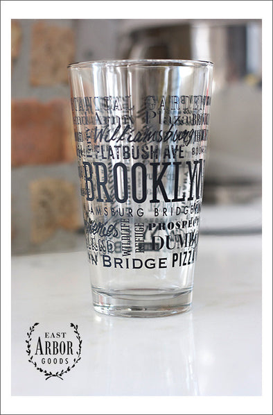 Pint Glass featuring Brooklyn, New York with highlights from the town in black screen print.