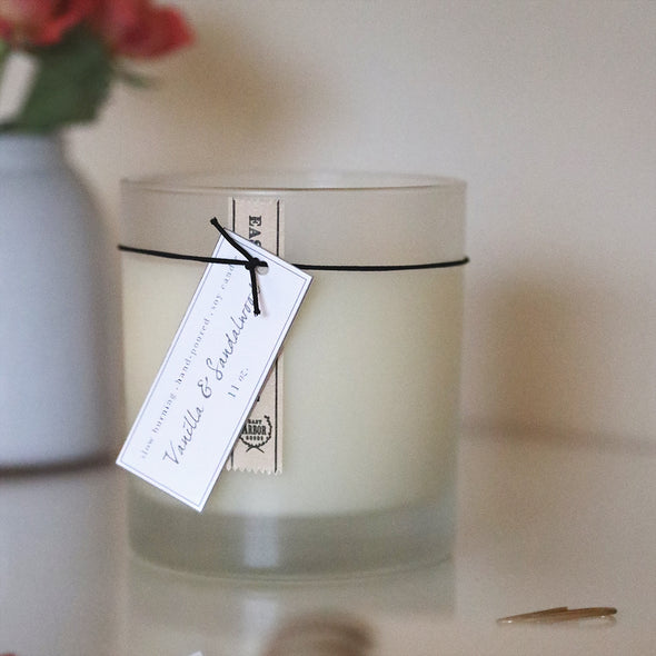Close up of frosted glass jar cream candle showcasing the hanging label detailing that the candle scent is Vanilla & Sandalwood. Candle on a home office desk with a vase of flowers in the background.