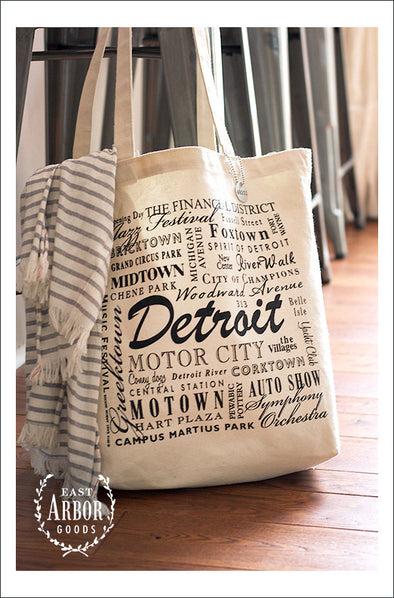Large natural colored canvas tote bag hanging from a chair with a shawl draped over the side. The bag has words in different fonts and sizes featuring places and activities connected to Detroit, Michigan.