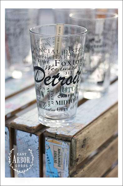 A group of pint glasses on a wood crate with one main one in focus featuring Detroit, Michigan with highlights from the town in black screen print.