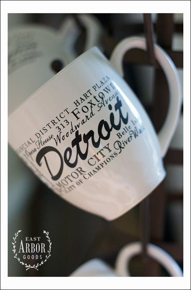 White ceramic coffee mugs hanging on a coffee mug stand focusing on one up close featuring Detroit, Michigan with places and activities featured in different fonts in black screen print.