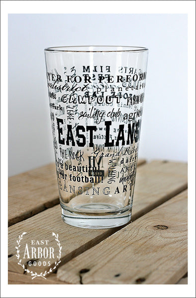 Pint Glass on wood crate. Glass features East Lansing, Michigan with highlights from the town in black screen print.