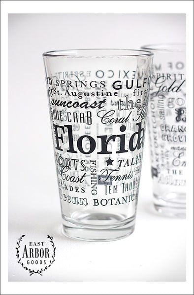 Two pint glasses with one in the center and main focus to show the black screen print details of words in different fonts and sizes featuring highlights of places and activities in Florida.
