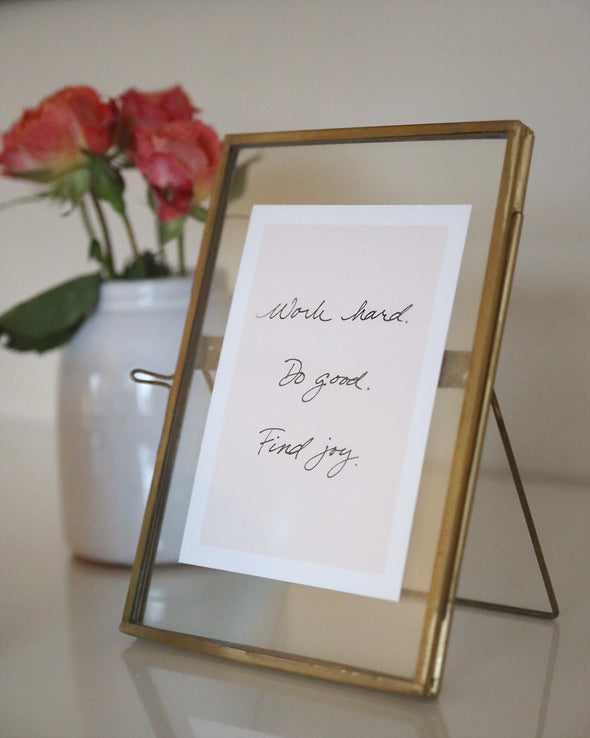 "Close up of an antique brass frame with clasp-detail with a small white card containing an inspirational quote. Card can be replaced with a 4""x6' photo of choice. Quote says ""Work Hard. Do Good. Find Joy."""