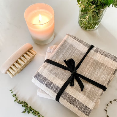 Close up view from above of a little cream candle in a frosted jar, a wooden handled scrub brush, a set of two folded linen towels wrapped with black fabric ribbon, and sprigs of fresh thyme as decorative accents.