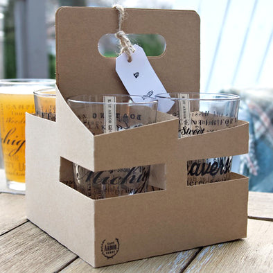 Cardboard carrying case with four pint glasses and a gift tag hanging from the top handle. Case sitting on top of an outdoor wood table with a pint glass filled with beer and a white deck chair in the background.