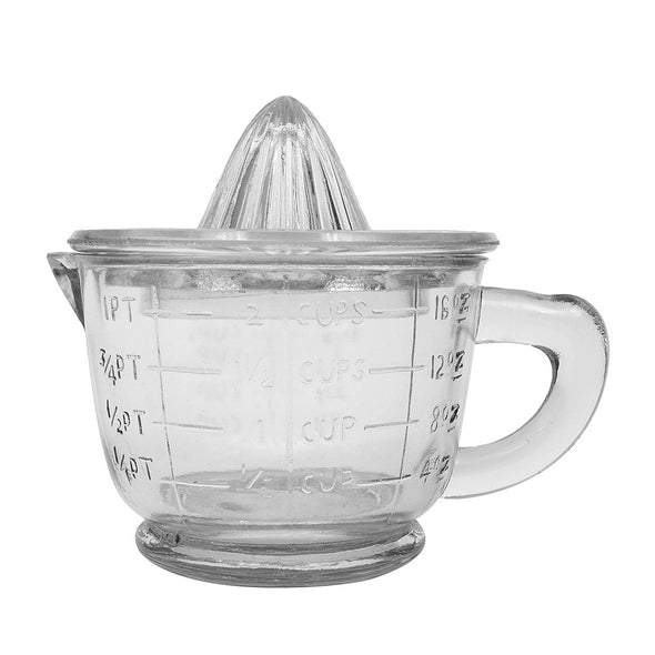 Close up of vintage farm-house thick-glass two-piece juicer set with a two cup measuring cup with handle and spout topped with a glass citrus juicer.