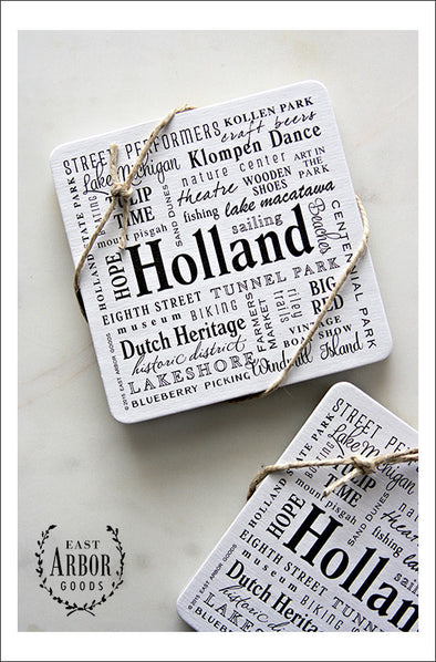 Two sets of drink coasters each tied with decorative twine shown featuring Holland, Michigan. Each set comes with 6 thick cardstock coasters with words in different fonts and sizes in black screen print.