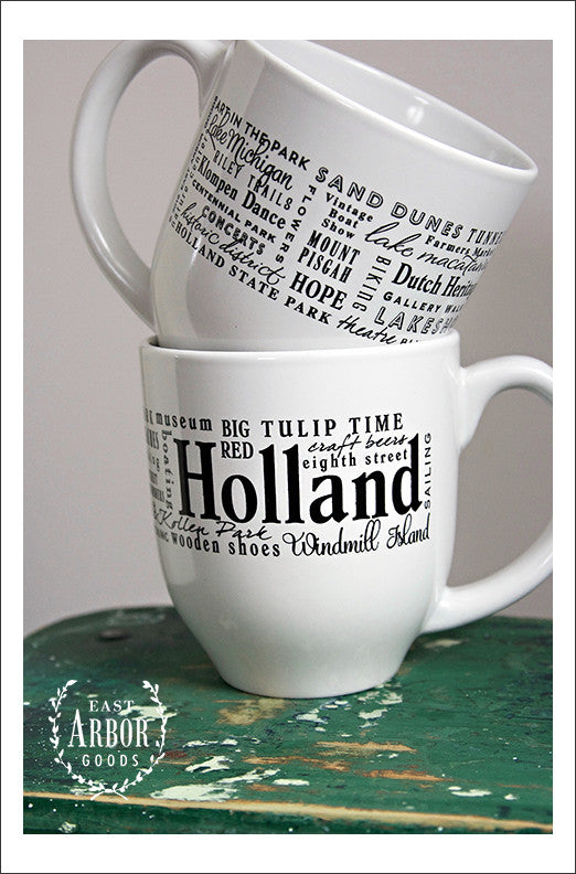 Two white coffee mugs with one stacked on top of the other -- one facing forward, the other with the back showing. The mugs feature Holland, Michigan with words in different fonts and sizes of places and activities from the area. Words are in black screen print.