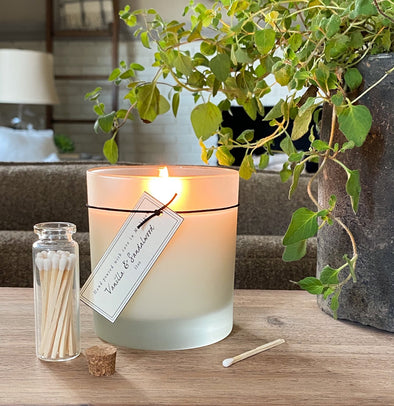 Lit frosted glass candle with long wooden matches that come in a glass apothecary jar with a little corked lid. Candle and matches jar on a natural wood table with the matches jar open, cork next to it, and one of the matches laying out to show the size.