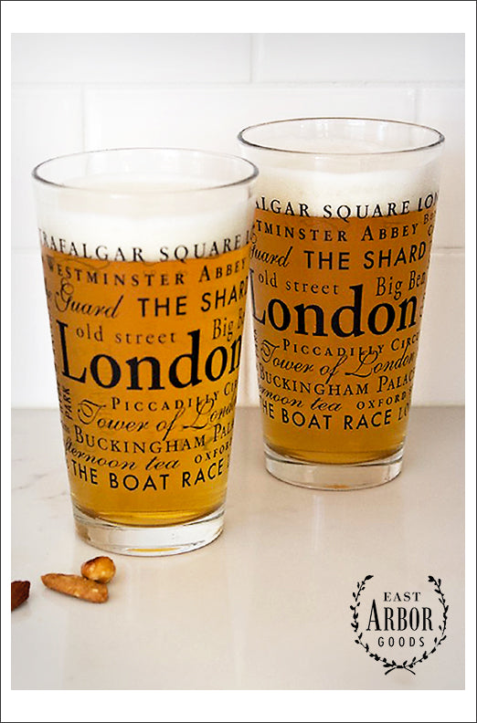 Two pint glasses next to each other filled with beer. Glasses have words in different fonts and sizes in black screen print around the theme of London, England.