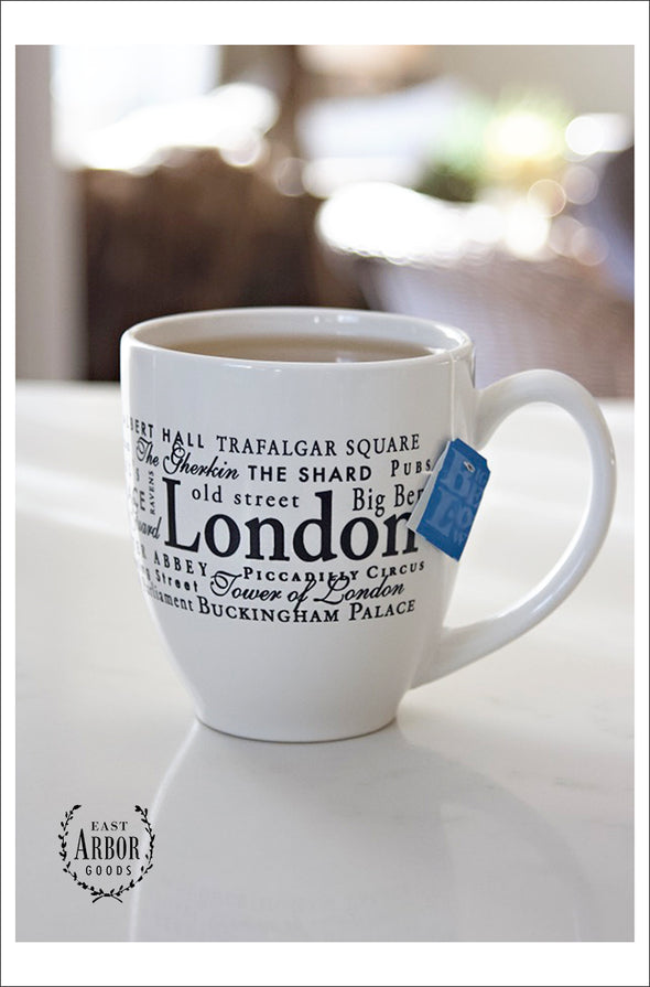 White ceramic mug filled with tea and a blue tea bag tag hanging over on a white countertop. Mug contains words in different fonts and sizes around the theme of London, England.
