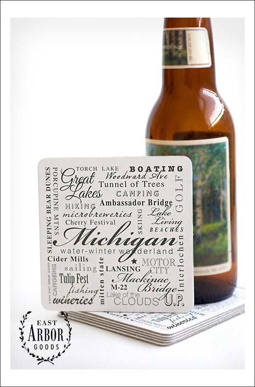 Stack of drink coasters with a glass beer bottle on top and one of the coasters leaning against the bottle to show the coaster design. The design is made up of words in different fonts and sizes around the theme of the state of Michigan.