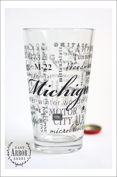 Close up of glass pint glass with design of multiple words around the glass. Words are in the theme of the state of Michigan including different places and activities connected to the state. Small red bottle cap behind the glass.