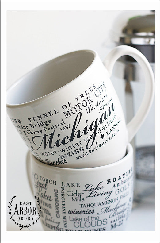 Two white coffee mugs with one stacked on top of the other -- one facing forward, the other with the back showing. The design on the mugs is made up of words in black screen print wrapped around in different fonts and sizes in the theme of the state of Michigan.