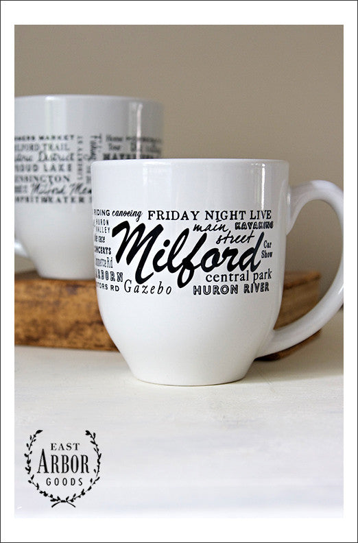 "Two white coffee mugs with one showing the front design of words wrapped around the mug in black screen print and in different fonts and sizes. In the middle is the word ""Milford"" for the town in Michigan. The other words represent places and activities in the area. The second cup is in the background on a book."