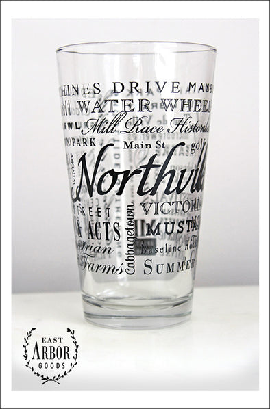 Pint Glass featuring Northville, Michigan with the word Northville in large script in the middle and words of places and activities in different fonts and sizes surrounding. All of the words in black screen print.