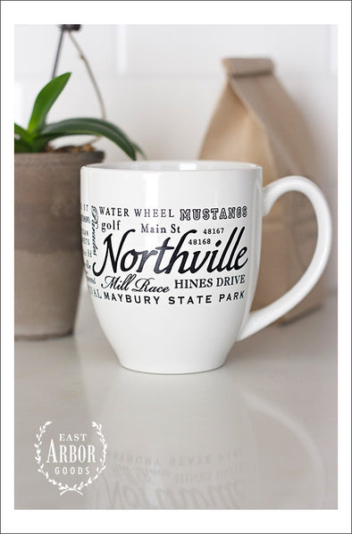 White ceramic coffee mug featuring Northville, Michigan with places and activities in different fonts and sizes in black screen print wrapped around the center of the mug. Placed on a white counter with a brown bag of coffee and plant in the background.