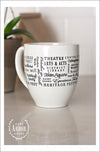 Back of white ceramic coffee mug featuring Northville, Michigan with places and activities in different fonts and sizes in black screen print wrapped around the center of the mug. Placed on a white counter with a brown bag of coffee and plant in the background.