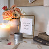 "Close up of a corner of a white home office desk containing a lit candle in a frosted glass jar, an antique 4""x6"" brass frame with clasp-detail containing a card with an inspirational quote, a medium-size white painted pottery vase filled with peach and pink flowers, and a small, circular metal canister with paperclips and binder clips with a few scattered on the desk."