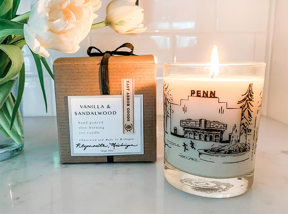 Lit cream colored candle in a glass jar with a hand drawn image of the Penn Theatre in Plymouth, Michigan. Next to lit candle is the brown gift box it comes in with white square label including the Vanilla & Sandalwood name and additional details. Both on a white kitchen countertop and part of white flowers in a vase on the left side.