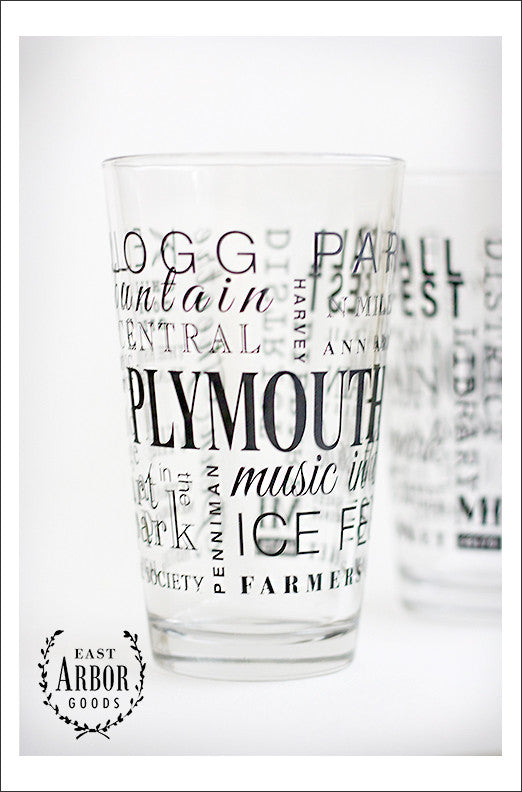 Two pint glasses with one in the center and main focus to show the black screen print details of words in different fonts and sizes featuring highlights of places and activities in Plymouth, Michigan.