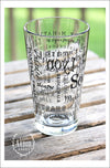 Left side view of Pint Glass featuring South Lyon, Michigan with highlights from the town in black screen print. On an outdoor wood plank table with green grass in the background.