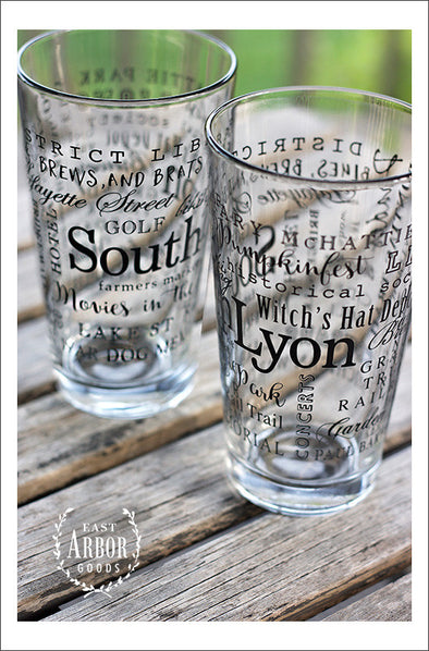"Two pint glasses next to each other on a wooden table and outdoor green grass background. Glass design is made up of words in black screen print and different fonts and sizes with the name ""South Lyon"" the largest and centered and the other words wrapping around the glass."