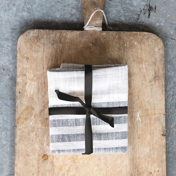 Set of three folded cream and black striped cotton kitchen towels wrapped with a black ribbon and placed in the middle of a rustic cutting board with handle.